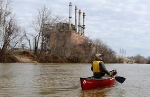 Mark Bishopric, a managing partner of Three Rivers Outfitters, paddles past the Duke Energy Dan River Steam Station on Tuesday. Source: John D. Simmons